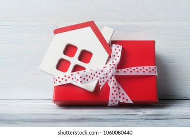 House model with gift box over white wooden background.