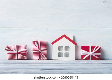 House model and gift boxes over white wooden background.