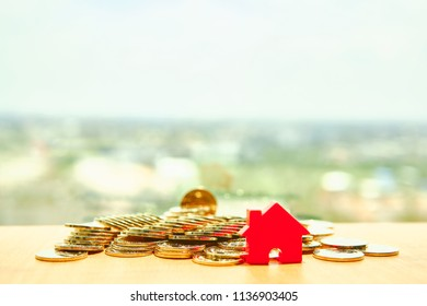 House model and gold coins placed on wooden boards.Home for cash.Credit or loan and earning for home in the family.Use money to exchange or buy in business and real estate.