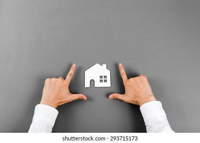 House model and human hand, gray background