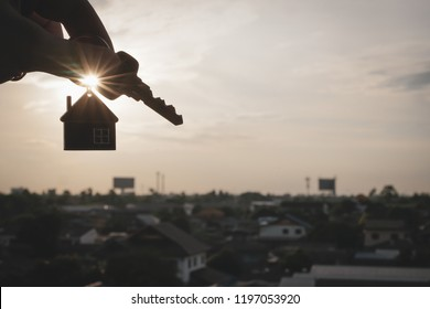 House model and key in home insurance broker agent 's hand or in salesman person. Real estate agent offer house, property insurance and security, affordable housing concepts