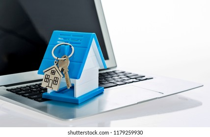 House model and key on laptop keyboard.