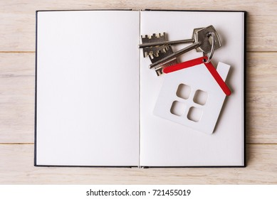 House model with keys on open blank page of sketchbook
