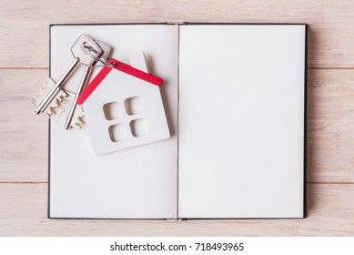 House model with keys over open blank sketchbook.