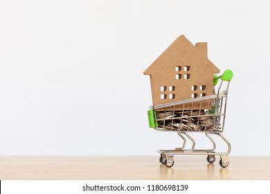 House model in mini shopping cart with stack of coins money on wooden table for residential investment. Concept for property ladder, mortgage and real estate investment