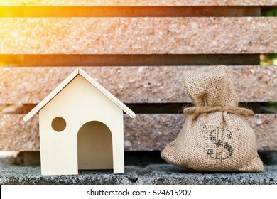 A house model and money bags for loans real estate concept.