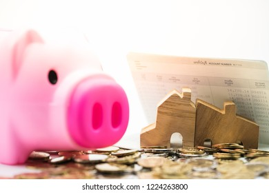 House model on bankbook and coins  from piggy bank. Concept for money saving for housing, property ladder, mortgage and real estate investment .