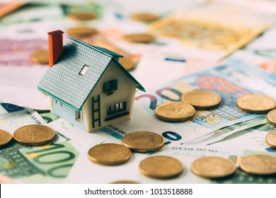 House model on cash stack closeup. Real estate property renting concept