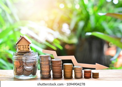 house model on coins saving set decrease down for concept interest rate low for home loan financial and mortgage