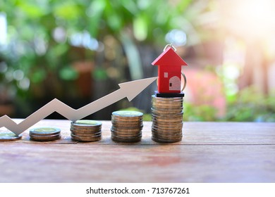 house model on coins saving for concept mortgage investment increase to profit finance and business