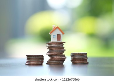 House model on coins stack. Property investment concept.