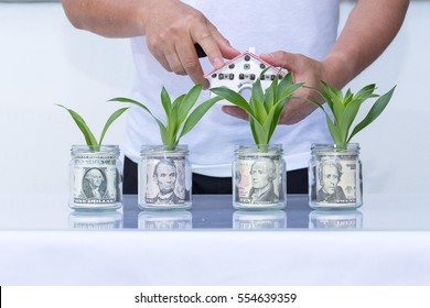 house model on dollar cash stack in jar glass or bottle glass closeup