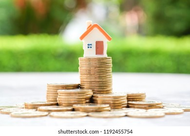House model on heap of coins. Property investment concept.
