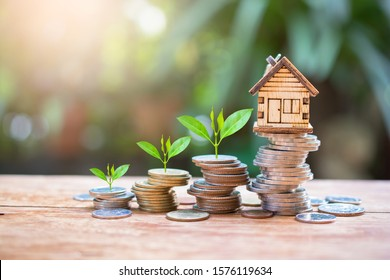house model on money coins saving for concept investment mortgage fund finance and home loan refinance