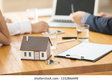 House model on wooden table in office of real estate