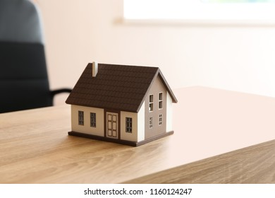 House model on wooden table. Mortgage concept
