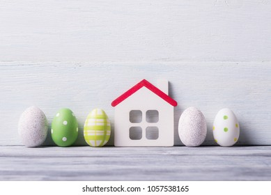 House model and painted Easter eggs on white wooden background.