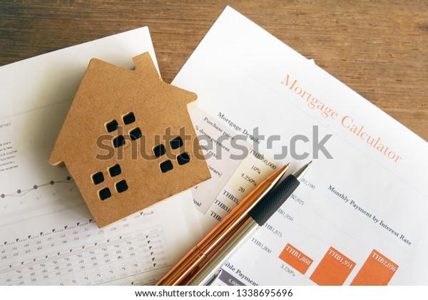 House model and pen on housing spending document