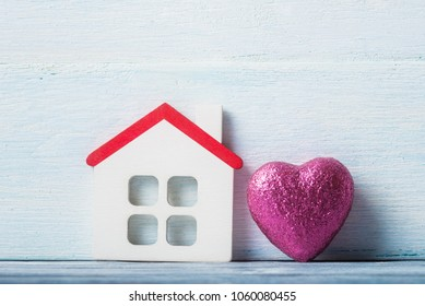 House model and pink heart on white wooden background.