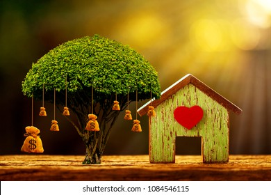 House model and red heart for family and big money bag of tree as destinations is saving put on the wood in the morning sunlight, Business investment or loan for real estate concept.