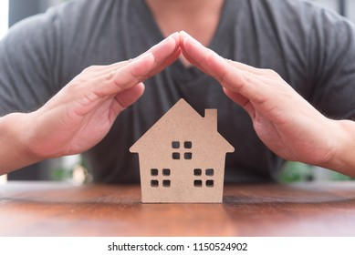house model in saving plan for residence of people in society, purchasing home for living of dream of community lives. hand protect house model in insurance cocept