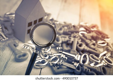house model with silver keys and hand with magnyfying glass,business real estate concept
