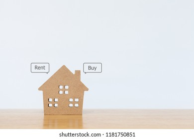 House model with speech bubble buy and rent on wooden table for residential investment. Concept for property, mortgage and real estate investment