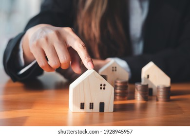 house model ,The hand of the businessman guarding close Money saving ideas to buy a home or loan for real estate investment planning and ideas during saving can be risky.