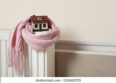 House model wrapped in pink scarf on radiator indoors, space for text. Heating efficiency