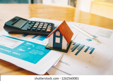 House model,Calculator and financial chart  on wooden table. Investment to buying property concept.