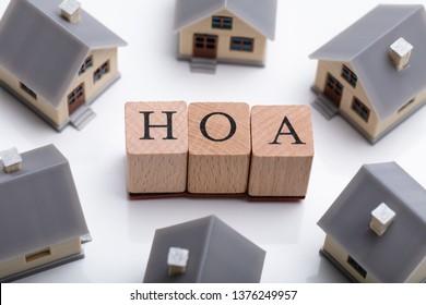 House Models Around HOA Cubic Blocks Over Reflective Desk