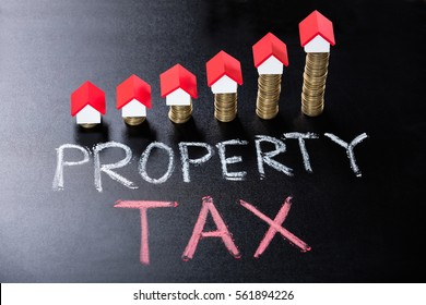 House Models On Stacked Coins Showing Property Tax Concept On Blackboard