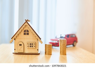 House models and red car models and gold coins placed on wooden boards.Credit or loan and earning for home and car in the family.Use money to exchange or buy in business and real estate.