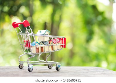 House models stacking on shopping cart. Concept for property ladder