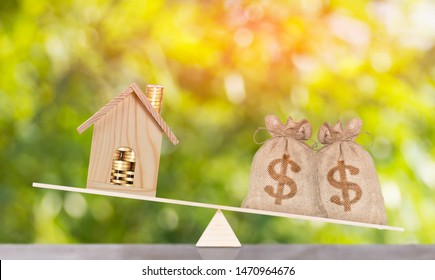 house and money bag put on the balance scales Saving for buy a new home or loan for plan business investment concept.
