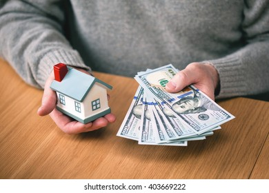 House and money. buy real estate, home mortgage. hands holding new hundred-dollar bills and toy house. Real estate agent