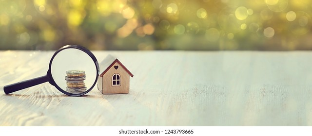 house and money. toy house, magnifying glass and coins. concept of mortgage, construction, rental housing. soft selective focus. banner
