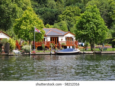 House and Moorings on the Banks of the River Thames in England with Union Flag flying