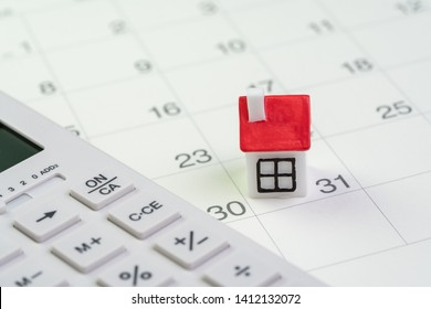 House mortgage payment and installment schedule concept, small miniature house on end of month calendar with calculator.