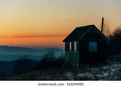 House in mountains with sunset