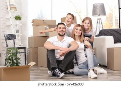 House move concept. Happy family sitting on the floor in new home