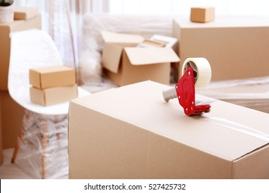 House moving concept. Packing cardboard box with sticky tape, closeup