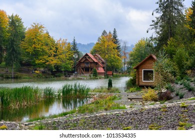 House near the lake in the forest, autumn day.  Leaf fall landscape.