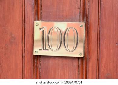 House number 100 brass sign on door