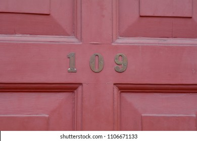 House number 109 sign on door painted red