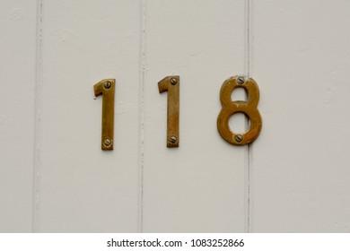 House number 118 sign on wooden door