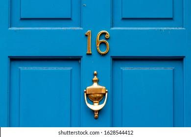 House number 16 on a blue wooden front door with door knocker