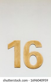 House number 16 on a white wall