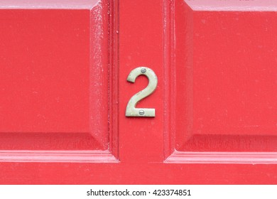 House Number 2 sign on red door