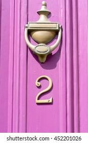 House number 2 sign on pink colour door with brass door knocker